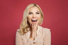 Piękna szczęśliwa z podnieceniem kobieta roześmiana i krzyczy na kolorowym różowym tle Zdziwiona dziewczyna z rozpieczętowanym us zdjęcia royalty free
