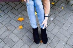 Piękna szczupła dziewczyna, kobieta siedzi na parkowej ławce prostuje, dotyka, ona nogi, cajgi, spodnia i buty, buty verdure pozy zdjęcia stock