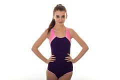 Piękna szczupła dziewczyna w ciała swimsuit spojrzeniach w kamerę i utrzymuje jej ręki na stronach obrazy stock