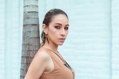Piękna szczupła kobieta odpoczywa na drzewku palmowym patrzeje kamerę w profilu, zielonych oczy i dobrego makeup fotografujących, Zdjęcia Royalty Free