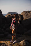 Piękna szczupła kobieta w koszula, skróty i moda okulary przeciwsłoneczni, chodzimy na dużych skałach Widok od plecy Piękno ślicz Obrazy Stock