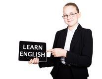 Piękna szkolna dziewczyna w garniturze trzyma komputer osobisty pastylkę w jego rękach i patrzeć w kamerę na komputer osobisty pa Zdjęcie Stock