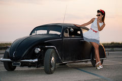 Piękna szpilki dziewczyna pozuje z gorącym drogowym samochodem Obraz Stock