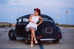 Piękna szpilki dziewczyna pozuje z gorącym drogowym samochodem Fotografia Royalty Free