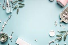 Piękna tło z twarzowymi kosmetycznymi produktami, liśćmi i czereśniowym okwitnięciem na pastelowym błękitnym desktop tle, fotografia stock