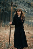 Piękna tajemnicza mistyczna dziewczyna trzyma warkocz w ciemnym jesień lesie na sposobie z długie włosy w czerni sukni Mistyczny  Obraz Royalty Free