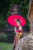 Piękna Tajlandzka dziewczyna w tradycyjnym smokingowym kostiumowym czerwonym parasolu jak obraz royalty free