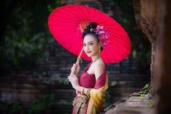 Piękna Tajlandzka dziewczyna w tradycyjnym smokingowym kostiumowym czerwonym parasolu jak obrazy stock