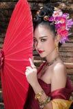 Piękna Tajlandzka dziewczyna w tradycyjnym smokingowym kostiumowym czerwonym parasolu jak fotografia royalty free