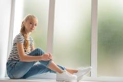 Piękna teenaged dziewczyna na nadokiennym parapetu profilu strzale fotografia royalty free