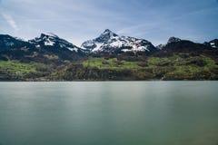 Piękna turkusowa halna jeziorna panorama z śnieżystymi szczytami, zielonymi łąki i lasy obrazy stock
