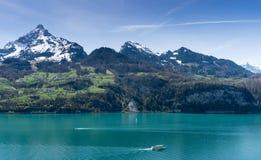 Piękna turkusowa halna jeziorna panorama z śnieżystymi szczytami, zielonymi łąki, lasy i łodzie na jeziorze fotografia royalty free
