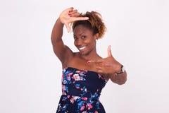 Piękna uśmiechnięta amerykanin afrykańskiego pochodzenia kobieta robi ramowym gestów wi Obrazy Royalty Free