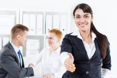Piękna uśmiechnięta biznesowa kobieta w kostium ofiary ręce trząść obraz stock