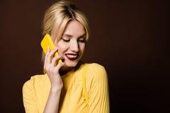 piękna uśmiechnięta blondynki dziewczyna opowiada żółtym smartphone fotografia royalty free