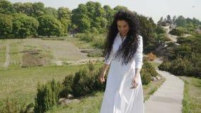 Piękna uśmiechnięta brunetka w biel sukni jest poruszająca up schodki zdjęcie wideo