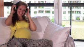 Piękna uśmiechnięta ciężarna caucasian kobieta używa hełmofon na jej dziecko garbku zbiory wideo