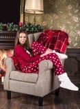 Piękna uśmiechnięta dziewczyna w czerwonych bożych narodzeniach stwarza ognisko domowe odzieżowe piżamy i bielu domu buty siedzą  fotografia royalty free