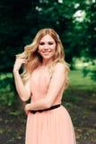 Piękna uśmiechnięta dziewczyna w różowej sukni na tle zieleni drzewa Fotografia Royalty Free