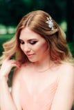 Piękna uśmiechnięta dziewczyna w różowej sukni na tle zieleni drzewa Obrazy Royalty Free