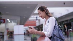 Piękna uśmiechnięta kobieta bierze przybywającego wezwanie telefon komórkowy wśrodku centrum handlowego zbiory