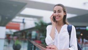Piękna uśmiechnięta kobieta bierze przybywającego wezwanie telefon komórkowy wśrodku centrum handlowego zdjęcie wideo