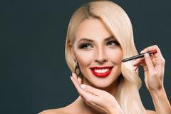 piękna uśmiechnięta kobieta robi czerwonym wargom z kosmetycznym ołówkiem, zdjęcia stock