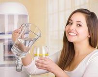 Piękna uśmiechnięta kobieta trzyma szkło woda w jeden ręce i miotaczu woda w jej innej ręce z filtrem, Fotografia Royalty Free