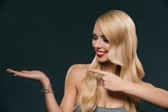 piękna uśmiechnięta kobieta wskazuje i przedstawia przy coś, fotografia stock