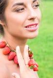 Piękna uśmiechnięta kobieta z czerwonymi koralikami i pierścionek robić świeża truskawka Zdjęcia Royalty Free