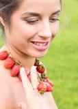 Piękna uśmiechnięta kobieta z czerwonymi koralikami i pierścionek robić świeża truskawka Zdjęcia Stock