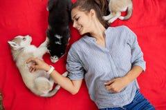 Piękna uśmiechnięta kobieta z ponytail i być ubranym pasiastą koszula cuddling z trzy słodkimi łuskowatymi szczeniakami podczas g obrazy stock