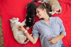 Piękna uśmiechnięta kobieta z ponytail i być ubranym pasiastą koszula cuddling z trzy słodkimi łuskowatymi szczeniakami podczas g zdjęcie royalty free