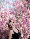 Piękna uśmiechnięta młoda kobieta blisko kwitnie wiosny drzewa Portret ładna blond dziewczyna z długie włosy w różowych kwiatach Obrazy Royalty Free