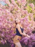 Piękna uśmiechnięta młoda kobieta blisko kwitnie wiosny drzewa Portret ładna blond dziewczyna z długie włosy w różowych kwiatach Fotografia Stock