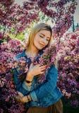Piękna uśmiechnięta młoda kobieta blisko kwitnie wiosny drzewa Portret ładna blond dziewczyna z długie włosy w różowych kwiatach Zdjęcie Stock