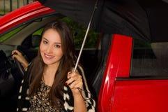 Piękna uśmiechnięta młoda kobieta jest ubranym wełny kurtkę, pozuje dla kamery i trzyma parasol w czerwonym samochodzie Zdjęcia Stock
