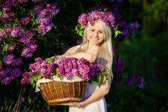 Piękna uśmiechnięta młoda kobieta jest ubranym wianek i kosz li Zdjęcie Stock
