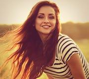 Piękna uśmiechnięta młoda kobieta patrzeje szczęśliwy z długimi zadziwiającymi brzęczeniami obraz stock