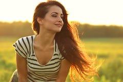 Piękna uśmiechnięta młoda kobieta patrzeje szczęśliwy z długimi zadziwiającymi brzęczeniami zdjęcie stock