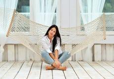 Piękna uśmiechnięta młoda kobieta relaksuje w hamaku w domu Zdjęcie Stock