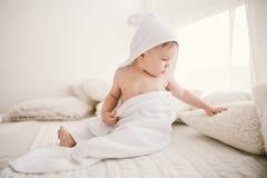 Piękna uśmiechnięta nowonarodzona chłopiec zakrywająca z białym bambusowym ręcznikiem z zabawa ucho Siedzący na białej dzianinie, Obrazy Royalty Free