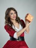 Piękna uśmiechnięta Santa pomagiera kobieta przedstawia Bożenarodzeniowego prezent patrzeje kamerę Obraz Royalty Free