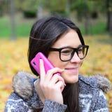 Piękna uśmiechnięta studencka dziewczyna opowiada na telefonie komórkowym zdjęcie stock