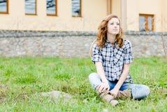 Dosyć ono uśmiecha się szczęśliwa nastoletnia dziewczyna siedzi outdoors Obrazy Stock