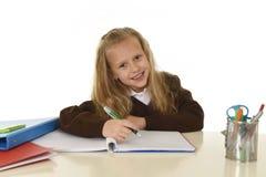 Piękna uczennica w mundurku szkolnym z blondynu uśmiechniętym szczęśliwym obsiadaniem na biurku robi pracie domowej Zdjęcia Stock