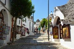Piękna ulica Alberobello z trulli domami wśród zielonych rośliien i kwiatów, główny turystyczny okręg, Apulia region, Southe Obraz Royalty Free