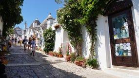 Piękna ulica Alberobello z trulli domami wśród zielonych rośliien i kwiatów, główny turystyczny okręg, Apulia region, Southe Zdjęcie Stock