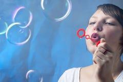 Piękna, urocza dziewczyna, dmucha mydlanych bąble na pięknym błękicie zdjęcie royalty free