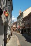 Piękna wąska ulica z plenerowymi kawiarniami w Vilnius starym mieście, Lithuania zdjęcie stock